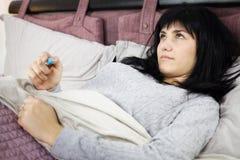 Mujer en infeliz enfermo de la sensación de la cama fotografía de archivo libre de regalías