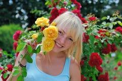 Mujer en jardín con las rosas Imágenes de archivo libres de regalías