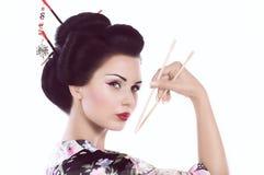 Mujer en kimono japonés con los palillos y el rollo de sushi Fotografía de archivo libre de regalías