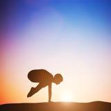Mujer en la actitud de la yoga de la actitud de la grúa que medita en la puesta del sol zen Fotos de archivo