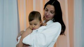 Mujer en la albornoz blanca que detiene al hijo en sus brazos almacen de video