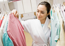 Mujer en la albornoz que mira en armario