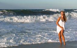 Mujer en la alineada blanca que presenta en la costa de mar Imagen de archivo