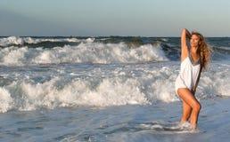 Mujer en la alineada blanca que presenta en la costa de mar Foto de archivo libre de regalías