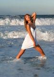 Mujer en la alineada blanca que presenta en la costa de mar Imagen de archivo libre de regalías
