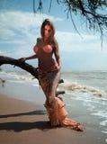Mujer en la alineada exótica que se coloca en la playa Fotografía de archivo