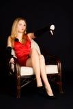 Mujer en la alineada roja que se sienta en la silla. Fotografía de archivo