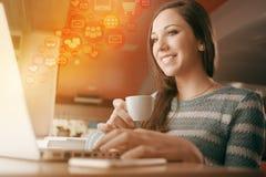 Mujer en la barra usando un ordenador portátil Fotografía de archivo