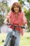 Mujer en la bici al aire libre que sonríe Fotos de archivo