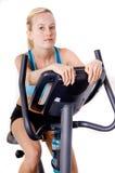 Mujer en la bici de ejercicios Imagen de archivo libre de regalías