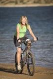 Mujer en la bici por el agua Foto de archivo libre de regalías
