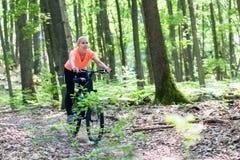 Mujer en la bicicleta de la bici de montaña Imagen de archivo