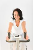 Mujer en la bicicleta del ejercicio Foto de archivo libre de regalías