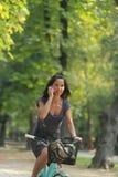 Mujer en la bicicleta del montar a caballo del teléfono Imagenes de archivo