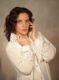 Mujer en la blusa blanca que habla en el teléfono Fotografía de archivo libre de regalías