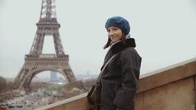 Mujer en la boina y el abrigo de invierno que se enfrían cerca de la torre Eiffel en París, Francia almacen de metraje de vídeo
