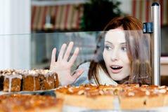 Mujer en la bufanda que mira el caso de cristal de la panadería Imagen de archivo libre de regalías