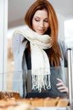 Mujer en la bufanda que mira la ventana de la panadería Imagen de archivo libre de regalías