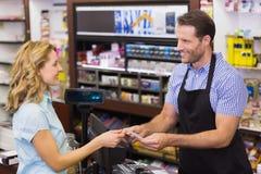 Mujer en la caja registradora que paga con la tarjeta de crédito Imágenes de archivo libres de regalías