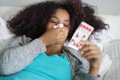 Mujer en la cama en casa que toma los antibióticos para la gripe Imagen de archivo