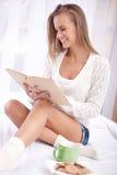 Mujer en la cama con el libro viejo y la taza de café Foto de archivo