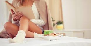 Mujer en la cama con el libro viejo y la taza de café Imágenes de archivo libres de regalías