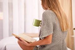 Mujer en la cama con el libro viejo y la taza de café Imagenes de archivo