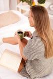 Mujer en la cama con el libro viejo y la taza de café Imagen de archivo