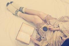 Mujer en la cama con el libro viejo y la taza de café en manos, punto de visión superior Copie el espacio para el texto Foto suav Imagen de archivo