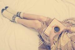 Mujer en la cama con el libro viejo y la taza de café en manos, punto de visión superior Copie el espacio para el texto Foto suav Fotografía de archivo