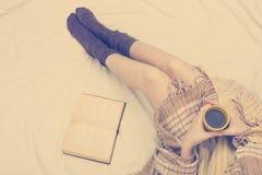 Mujer en la cama con el libro viejo y la taza de café en manos, punto de visión superior Copie el espacio para el texto Foto suav Fotos de archivo libres de regalías