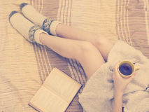 Mujer en la cama con el libro viejo y la taza de café en manos, punto de visión superior Copie el espacio para el texto Foto suav Fotografía de archivo libre de regalías