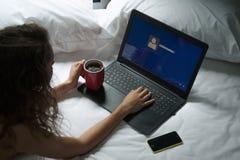 Mujer en la cama con el ordenador portátil y una taza de café Fotografía de archivo libre de regalías