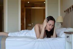 Mujer en la cama, llevando a cabo la cabeza con las manos, dolor de cabeza, jaqueca, resaca, vecinos ruidosos fotos de archivo libres de regalías