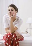 Mujer en la cama que desgasta los pijamas rojos del punto de polca Fotografía de archivo libre de regalías