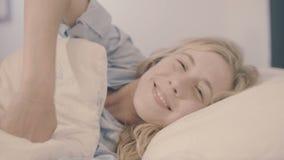 Mujer en la cama que despierta estirar y que sonríe en la cámara metrajes