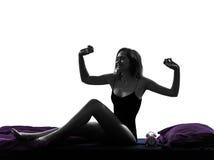 Mujer en la cama que despierta la silueta que estira feliz Fotos de archivo libres de regalías