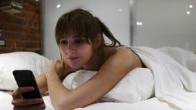 Mujer en la cama que miente en el estómago que hojea en Smartphone en la noche almacen de metraje de vídeo