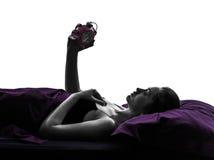 Mujer en la cama que mira la silueta del despertador Imagenes de archivo