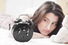 Mujer en la cama que mira un reloj Imagenes de archivo