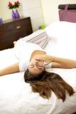 Mujer en la cama que pone el bostezo cansado Foto de archivo