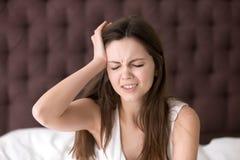 Mujer en la cama que sufre de dolor de cabeza por mañana Foto de archivo libre de regalías