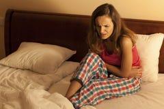 Mujer en la cama que tiene calambres abdominales Foto de archivo libre de regalías