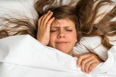 Mujer en la cama que tiene dolor de cabeza en la mañana Imagen de archivo