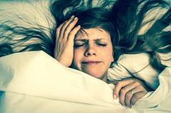 Mujer en la cama que tiene dolor de cabeza en la mañana - estilo retro Foto de archivo