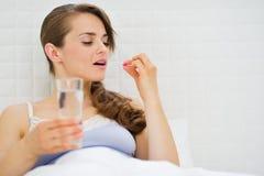 Mujer en la cama que toma píldoras Imágenes de archivo libres de regalías
