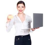 Mujer en la camisa blanca con el ordenador portátil y la tarjeta de crédito Imágenes de archivo libres de regalías