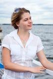 Mujer en la camisa blanca con las gafas de sol que se colocan en cubierta del buque Imágenes de archivo libres de regalías