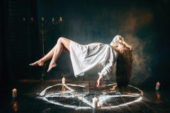Mujer en la camisa blanca que vuela sobre círculo del pentagram Foto de archivo libre de regalías