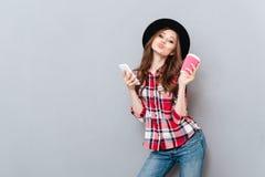 Mujer en la camisa de tela escocesa que sostiene el teléfono móvil y la taza de café Fotografía de archivo